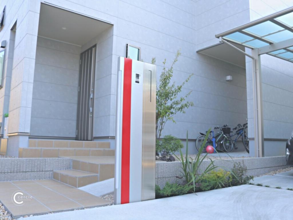 赤い門柱が際立つモダンなアプローチ